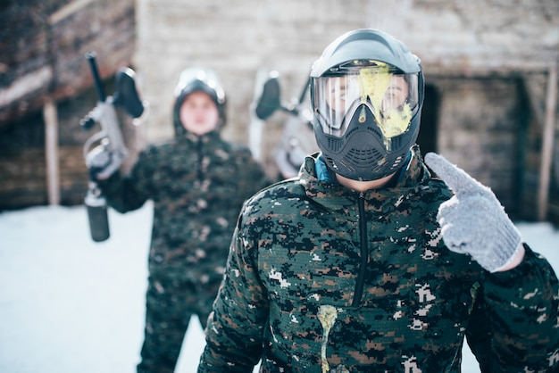 Paintball player points finger at splattered mask, team after winter battle. extreme sport game, soldiers in special uniform, paintballing
