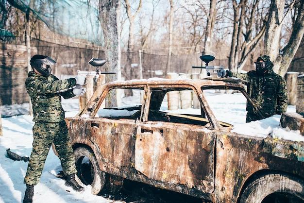 Пейнтболисты стреляют из-за сгоревшей машины