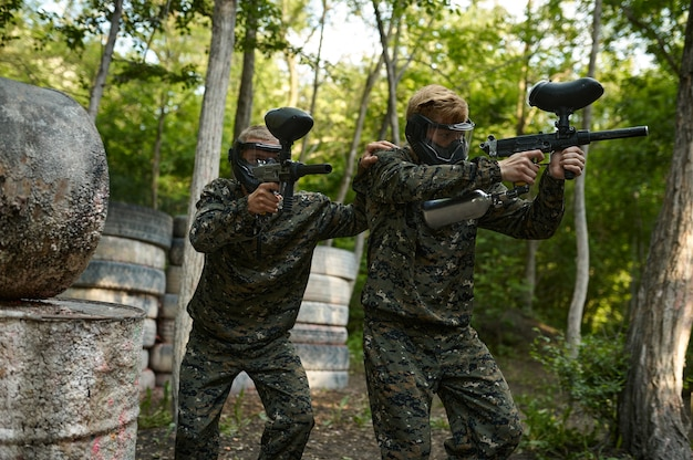 Paintball players in uniform and masks in forest