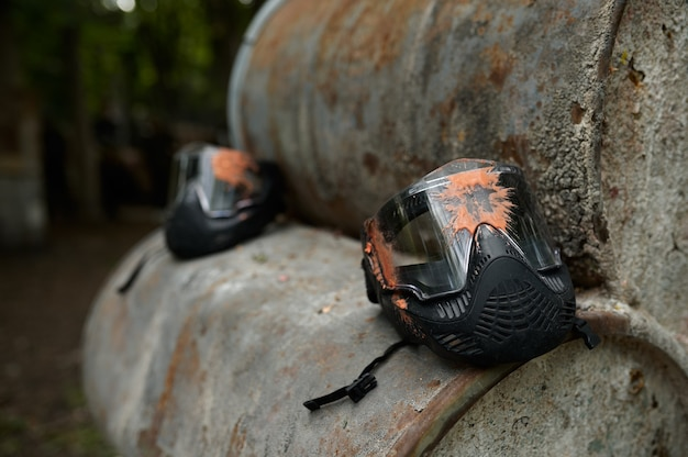 Paintball protection mask closeup, nobody, playground in the forest on background. extreme sport outdoors, pneumatic weapon and paint bullets, military team game concept