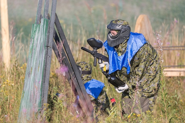 Paintball sport players in protective uniform and mask playing and shooting with gun outdoors.