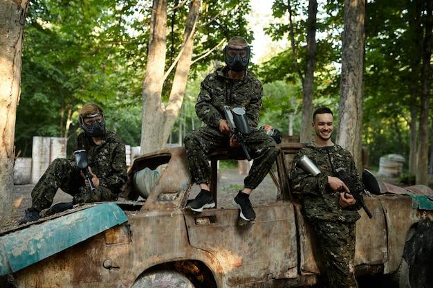 Пейнтбольная команда, друзья позирует у ржавой машины на детской площадке в лесу
