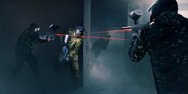 Пейнтбольная команда в бою, орудия с лазерным прицелом. экстремальная спортивная игра, игроки в защитных масках и камуфляже держат оружие в руках