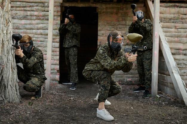Пейнтбольная команда в камуфляже и масках сражается на детской площадке в лесу. экстремальный спорт с пневматическим оружием и красящими пулями или маркерами, военная игра на открытом воздухе, тактика ведения боя