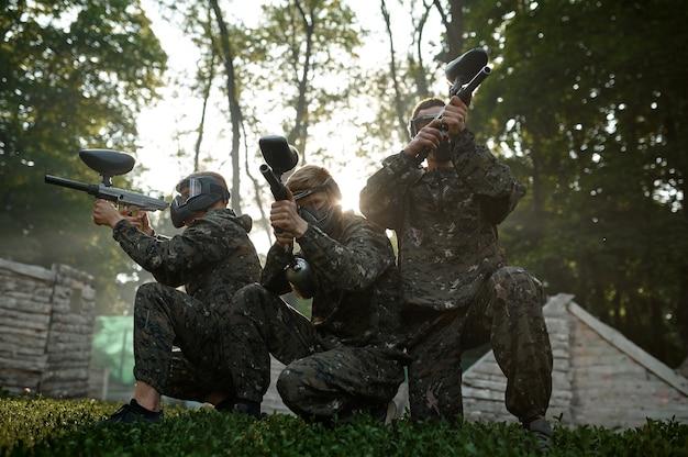 Пейнтбольная команда в масках, бой на детской площадке в лесу. экстремальный спорт с пневматическим оружием и красящими пулями или маркерами, военная игра на открытом воздухе, тактика боя