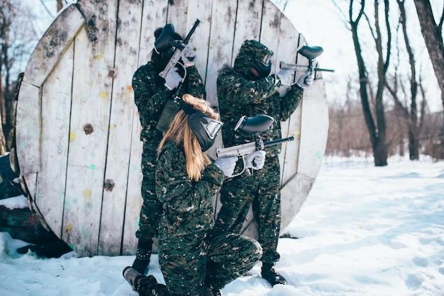 Пейнтбольная команда в форме и масках стреляет по врагу, вид сбоку, бой в зимнем лесу. экстремальная спортивная игра