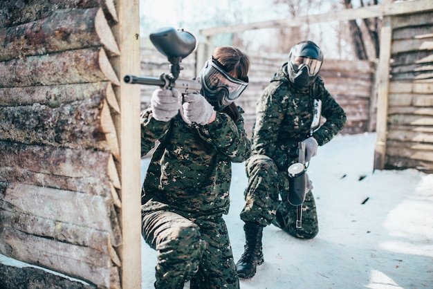 Paintball team, players in winter battle. extreme sport game, soldiers in protection masks and camouflage holds weapon in hands