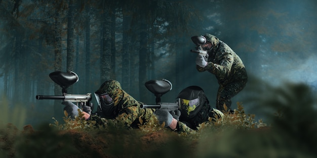 Paintball team shooting in forest battle. extreme sport game, players in protection masks and camouflage lies on the ground and holds weapons in hands