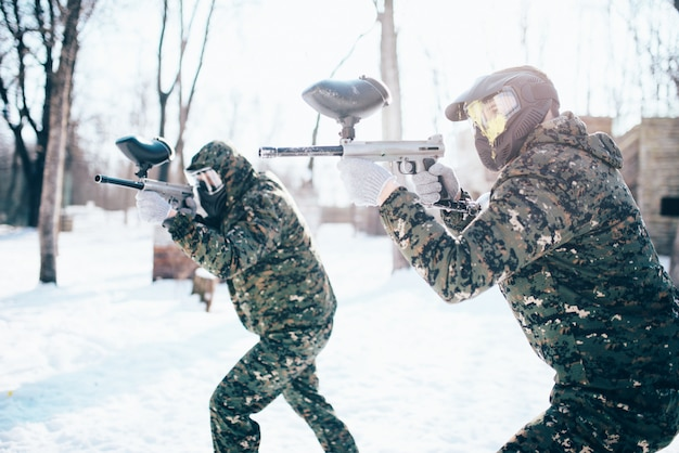 Paintball team in uniform attack in winter battle. extreme sport game, soldiers in protection masks and camouflage holds weapon in hands