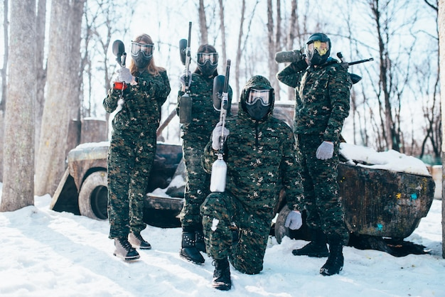 Paintball team in uniform and masks poses with marker guns in hands after winter forest battle. extreme sport game