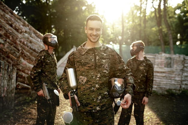 Paintball team, warriors poses on playground in the forest