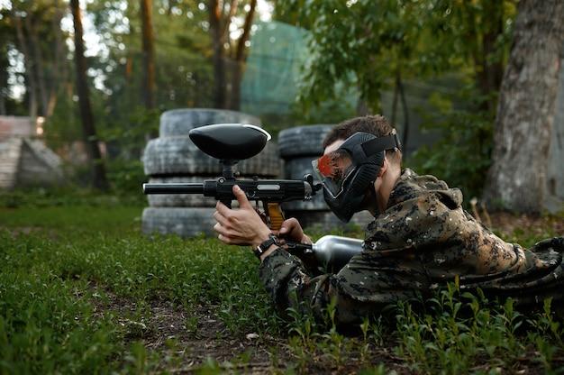 Пейнтбол воин стреляет, лежа на траве