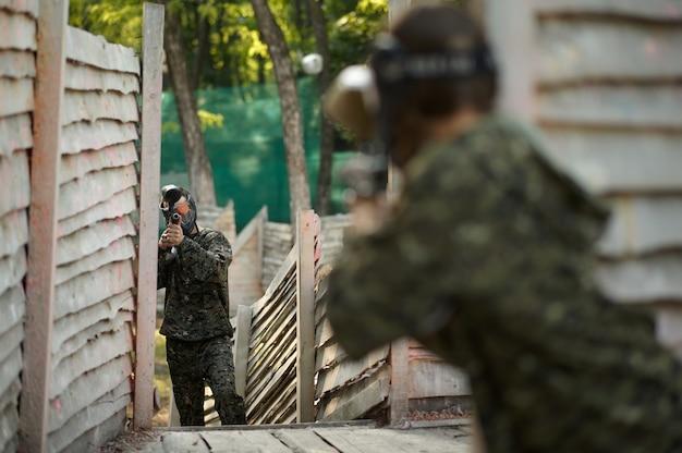 Пейнтбол воин стреляет из пистолета из приюта