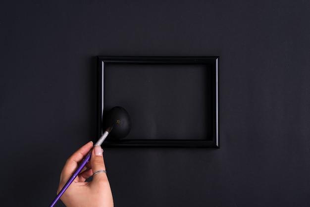 Рука женщины красит пасхальное яйцо paintbrash в черном цвете на такой же рамке и предпосылке фото цвета.