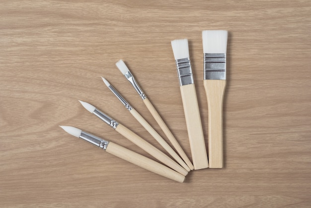 Paintbrush on brown wood table.using for arts and education