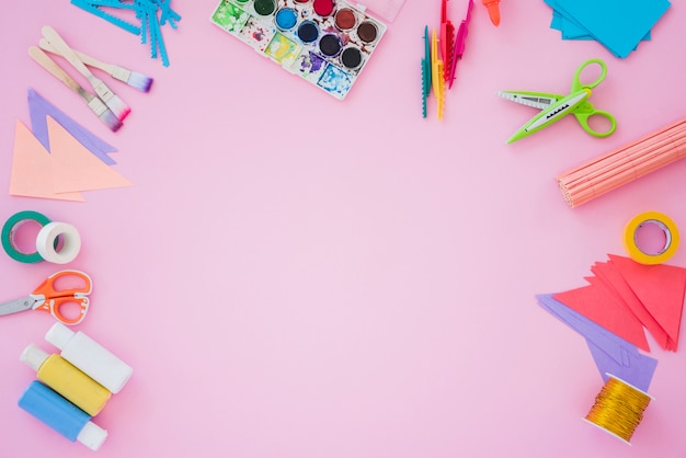 Paintbrush; color palette; scissor; golden spool; paper and scissor on pink backdrop