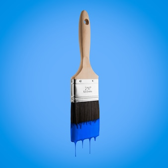 Paintbrush loaded with blue color dripping off the bristles- Isolated on blue background.