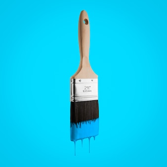 Paintbrush loaded with blue sky color dripping off the bristles