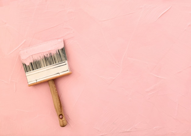Paintbrush on pink background with freshly painted texture