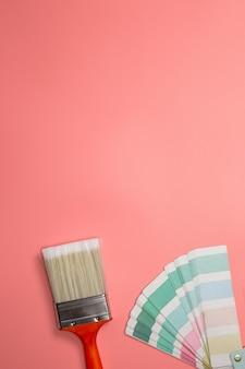 Кисть с палитрой для рисования образца пастельными цветами на розовом фоне, вид сверху, плоская планировка, пространство для копирования, фоновое пространство для текста