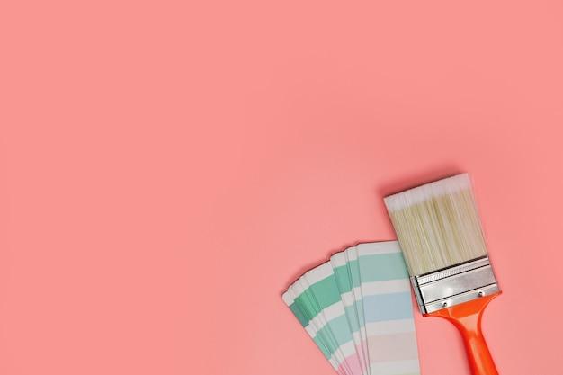 Кисть с палитрой для рисования образца пастельными цветами на розовом фоне, вид сверху, плоская планировка, пространство для копирования, концептуальное фоновое пространство для текста