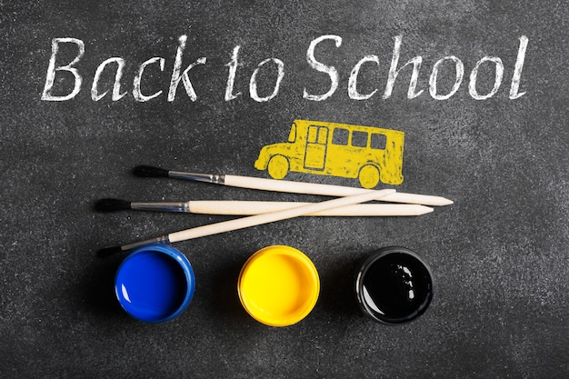 Paintbrushes and paints. back to school inscription