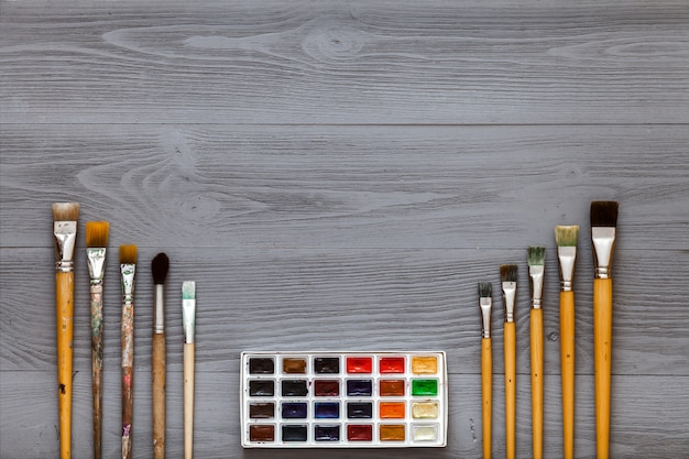 Набор кистей и акварельные краски на сером деревянном столе