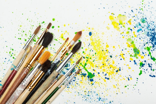 Paintbrushes and water-color abstract art close up