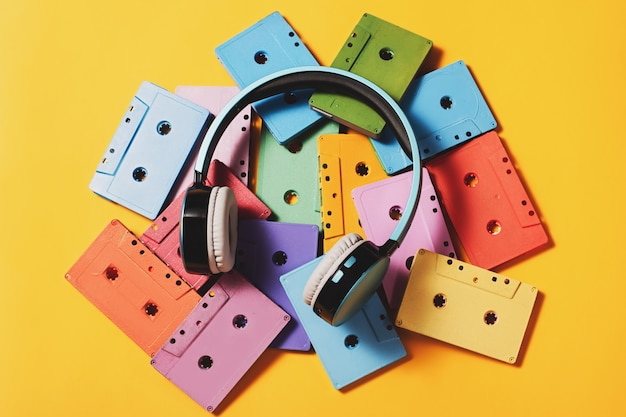 Painted audio cassettes and blue headphones on bright yellow surface