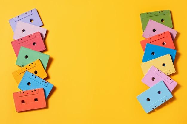 밝은 노란색 배경에 칠해진 오디오 카세트 프레임, 복사 공간, 위쪽 보기. 레트로 음악적 배경