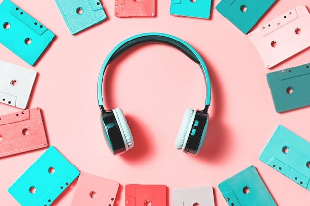밝은 색상으로 칠해진 오디오 카세트와 파스텔 배경에 파란색 이어폰, 복사 공간, 위쪽 전망. 레트로 음악적 배경입니다. 레트로 오디오 테이프 카세트, 80년대 배경, 파스텔 레트로 플랫 레이