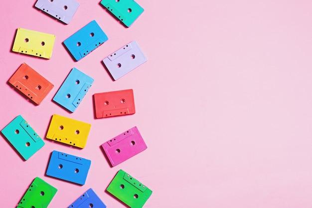 파스텔 배경, 복사 공간, 위쪽 전망에 밝은 색상으로 칠해진 오디오 카세트. 레트로 음악적 배경입니다. 레트로 오디오 테이프 카세트, 80년대 배경, 파스텔 레트로 플랫 레이