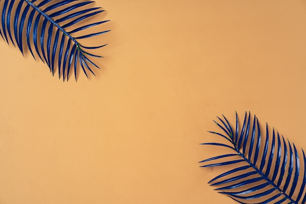 Painted blue palm leaves on beige background top view