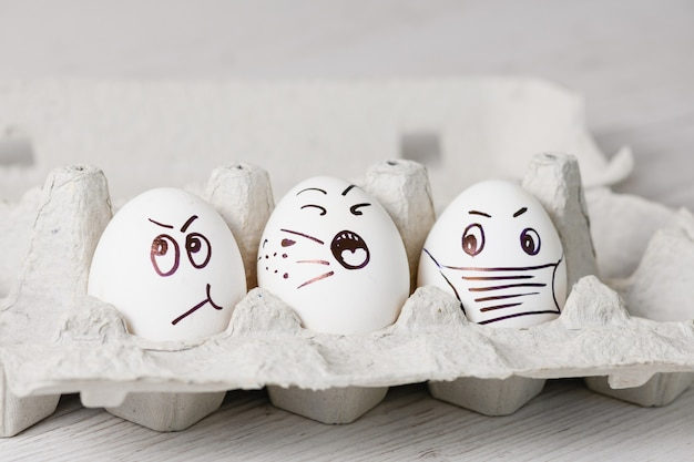面白い感情的な顔を持つマーカーの白い卵によって描かれたは、流行のコロナウイルスの春の休暇のために紙のトレイにクローズアップします。