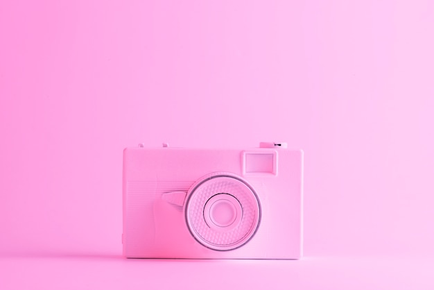 Painted camera against pink background with copyspace for writing the text