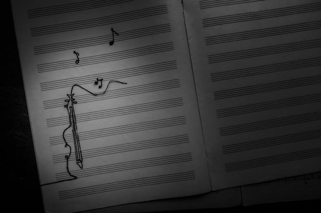 Раскрашенная виолончель с нотами на фоне музыкальной тетради джазовый день концепции