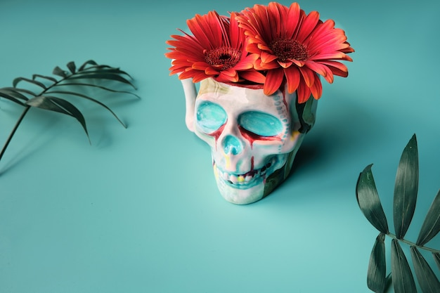 Расписанный керамический череп с яркими красными цветами ромашки герберы. украшение dia de los muertos.