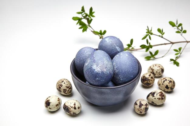 흰색에 녹색 잎을 가진 그릇과 가지에 그려진 닭고기와 메추라기 달걀