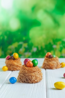 Painted chocolate eggs in sweet nests on white background