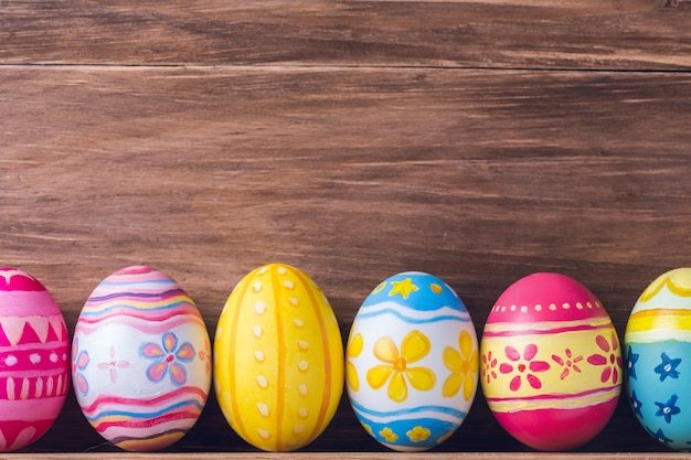 Painted colorful easter eggs on brown wood background