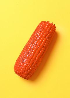 Окрашенная кукуруза на желтой поверхности