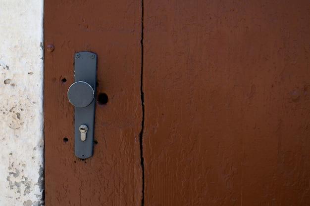 Крашеная дверная ручка и замочная скважина коричневой двери сарая. пустое пространство