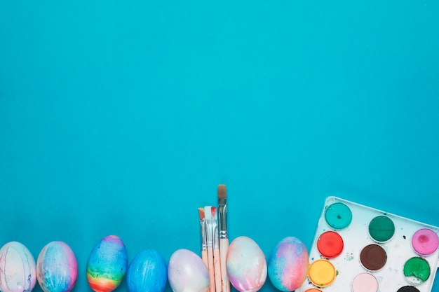 Painted easter eggs; brushes and water color paint box on the blue backdrop with copy space