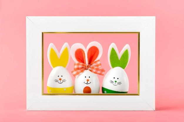 コーラルピンクの背景に笑顔の顔、耳、弓、白のフォトフレームとイースターエッグのかわいいウサギを描いた。