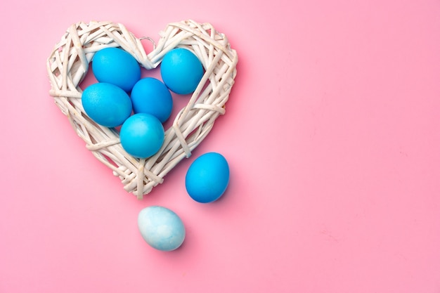 Painted easter eggs in decorative nest on pink background close up