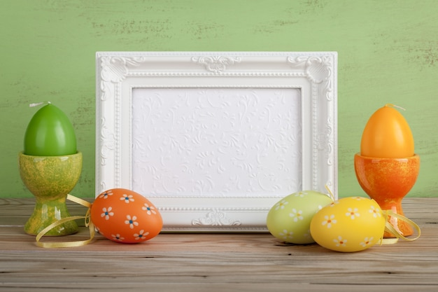 Painted easter eggs, eggs candles and white frame on green wooden background