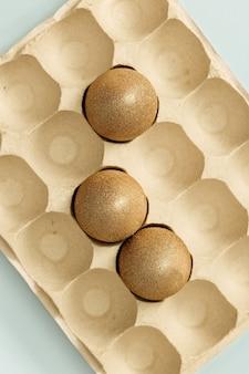 卵箱に金色の塗装イースターエッグ。最小限のイースターの概念。