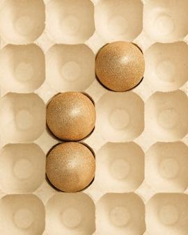 Раскрашенные пасхальные яйца золотого цвета в коробке для яиц. минимальная концепция пасхи.