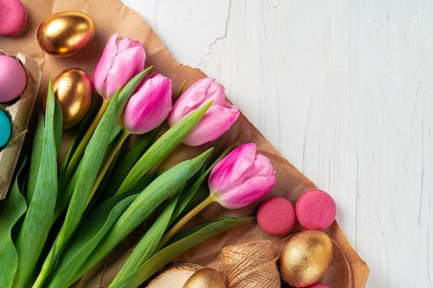 新鮮なチューリップと卵箱に描かれたイースターエッグをクローズアップ
