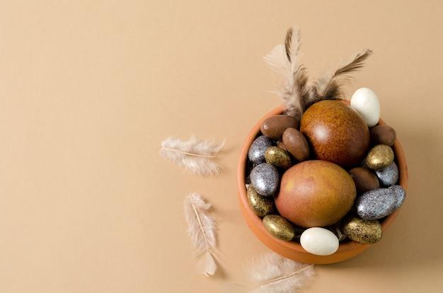 그려진 부활절 달걀은 갈색 그릇, 작은 사탕 달걀에 놓여 있습니다.
